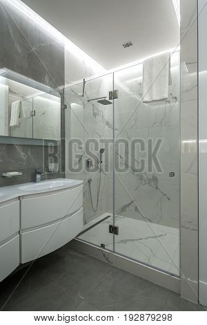 Light bathroom with textured tiled walls. There is a shower with a glass door, white sink with a faucet, mirror, luminous lamps, hanging towel. Indoors. Vertical.
