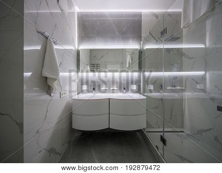 Stylish modern bathroom with light tiled walls. There is a shower with a glass door, two white sinks with faucets, mirror with backlight, luminous lamps, hanger with a towel. Indoors. Horizontal.