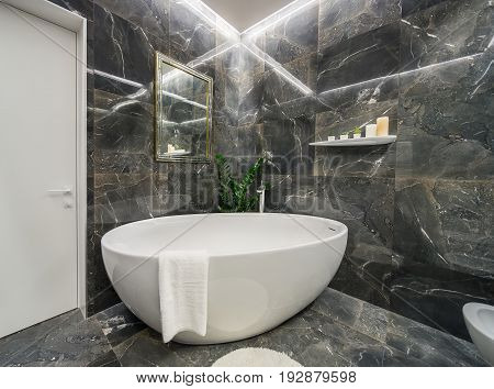 Luminous bathroom in a modern style with textured dark tiles. There is big white bath with a faucet and a towel, fancy mirror, small carpet, shelf with plants in the pots and candles, door. Indoors.