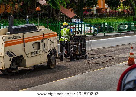Worker Fills A Handbarrow With Bitumen And Asphalt Paver Machine