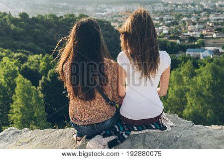 two women sitting on the peak and lookin on city landscape on sunset