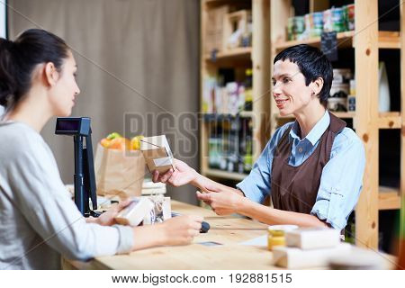 Helpful middle-aged shop assistant giving advice to customer while standing at counter in small store with organic food