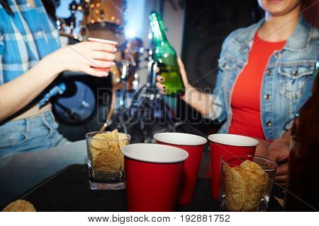 Mid section portrait of two modern girls drinking beer behind table with beer cups and snacks
