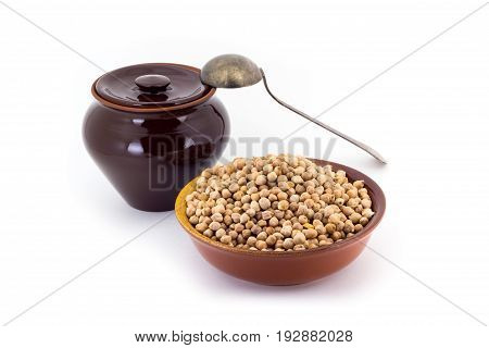 Still life of chick peas in ceramic pial, ceramic pot, old spoon , isolated on white background