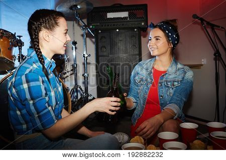 Portrait of two beautiful  girls clinking beer bottles at night club party
