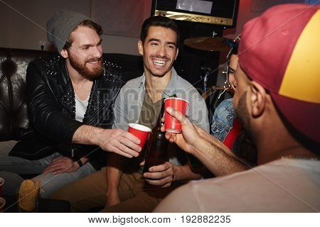 Group of smiling young people raising beer glasses hanging out at party and having fun
