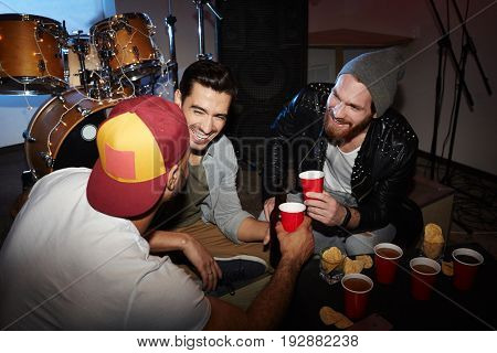 Group of trendy young men hanging out at party in club, drinking beer laughing and having fun