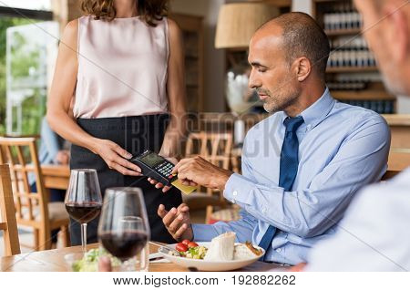 Waiter holding credit card swipe machine while customer typing code. Mature businessman making payment in cafe through credit card. Customer paying bill of lunch with debit card.
