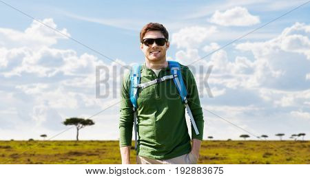 travel, tourism and people concept - happy young man in sunglasses with backpack over african savannah background