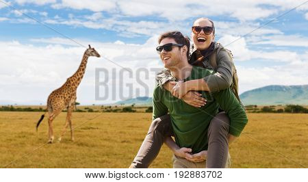 travel, tourism and people concept - happy couple with backpacks having fun over african savannah and giraffe background