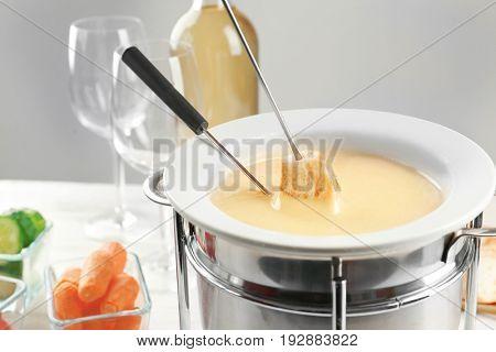 Piece of bread dipped into cheese fondue, closeup