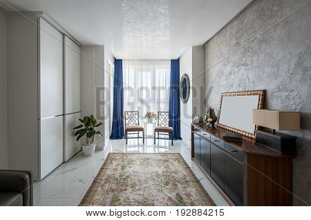 Hall in a modern style with light walls and tiled floor with carpet with flower patterns. There are two stylish chairs, round table, plants in vases, fancy mirror, wooden stand with drawers, lockers.