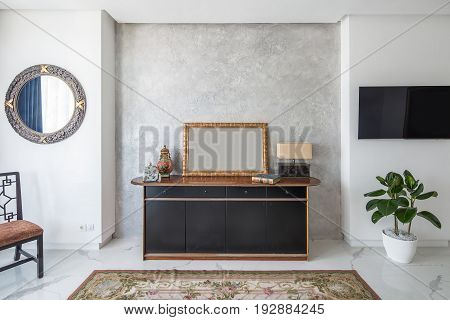 Room in a modern style with white walls and light tiled floor with a carpet with flower patterns. There is a stylish chair, fancy mirror, wooden stand with drawers, design lamp, decoration, plant, TV.