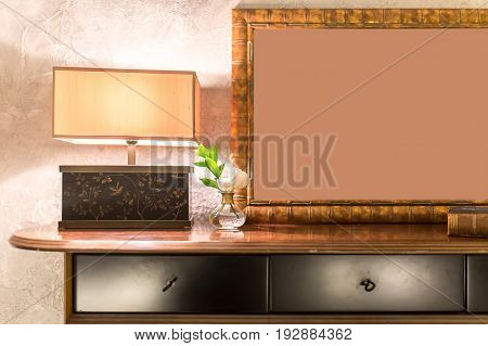 Wooden table with dark drawers on the textured light wall background. On the table there is a luminous fancy lamp, flowers in a vase, book and a bronze frame. Closeup. Indoors. Horizontal.
