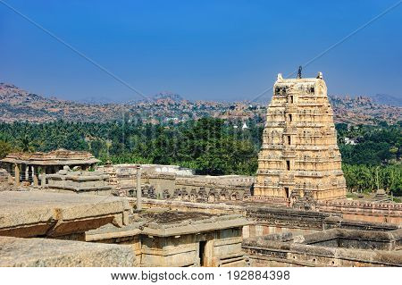 View of ancient ruins on Hemakuta hill in Hampi, Karnataka, India. Landscape with unique mountain formation with amazing stones, tropical nature and temple. UNESCO World Heritage Site