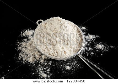 Sieve with flour on black background