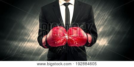 An elegant businessman dressed in suit clashing the boxing gloves on his hand with sparkle concept.