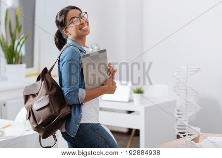 After biology class. Delighted young female student holding her bag and notes and smiling while standing in the scientific laboratory