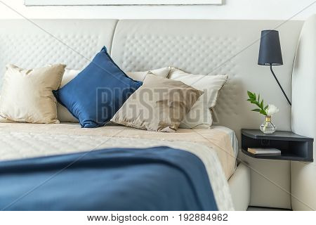 Wide bed with multicolored pillows and coverlets on the white wall background. On the right there is a black shelf with a flower in a glass vase and a book, lamp. Closeup. Indoors. Horizontal.