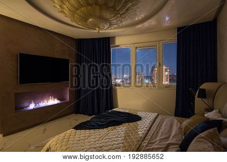 Bedroom in a modern style with a big fancy golden chandelier on the ceiling. There is a bed with pillows and a coverlet, burning fireplace, TV on the wall, windows with curtains. Indoors. Horizontal.