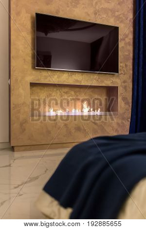 Textured bronze wall with a fireplace with a burning fire and a big TV. There is a bed with a blue coverlet in front of the wall. On the floor there are light tiles. Closeup. Indoors. Vertical.