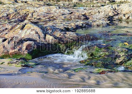 Coast of the Andaman Sea with sea and rock in Nang Thong Beach, Khao Lak, Thailand. Rapid flow of water through the rocks covered with algae. Nature composition