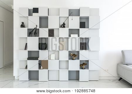 Interior in a modern style with white walls and light tiled floor. There is a geometric stand with many shelves with decoration figures, books and a black vase. On the right side there is a gray sofa.