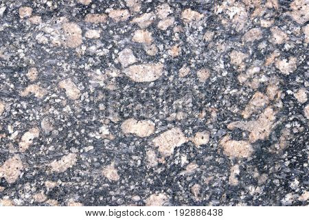 Stone Background of mottled granite igneous rock used for kitchen worktops etc. Inclusions of large light pinkish stones