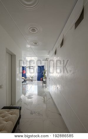 Light corridor in a modern style with textured walls and a tiled floor. There is a hall with tables, flowers in a vases, sofas, lamps. stand, door, windows with curtains. Indoors. Vertical.