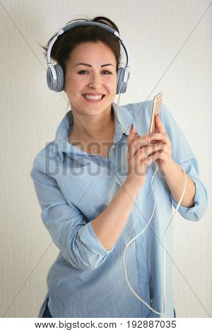 Beautiful woman listening to music on light background