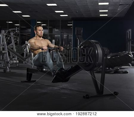 Portrait of muscular athlete working on rowing machine in modern fitness center.Cross training