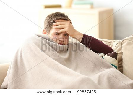 Young ill man covered with plaid at home