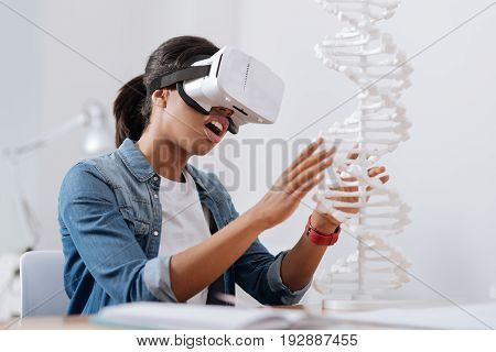 Modern science. Nice pleasant intelligent woman sitting at the table in the 3d glasses and looking at the gene model while studying microbiology