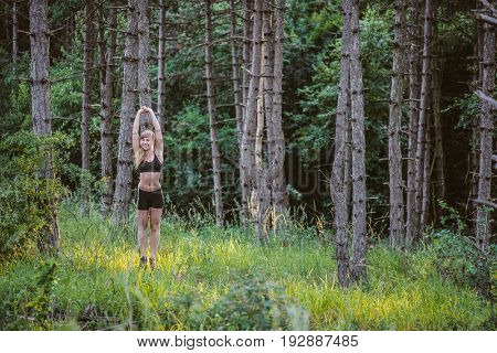 Sporty woman doing exercise in forest. Arms raised.