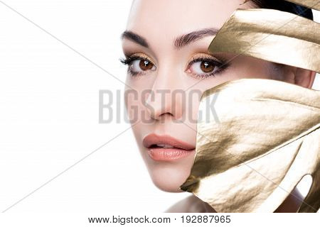 Obscured View Of Woman Covering Face With Big Golden Leaf Isolated On White