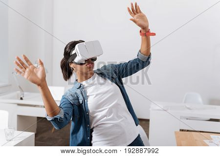 Age of technology. Attractive nice pleasant woman standing in the room and being in virtual reality while using 3d technology