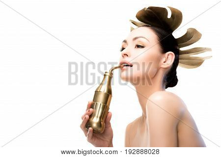Side View Of Woman With Golden Leaf And Water Bottle Looking Away Isolated On White