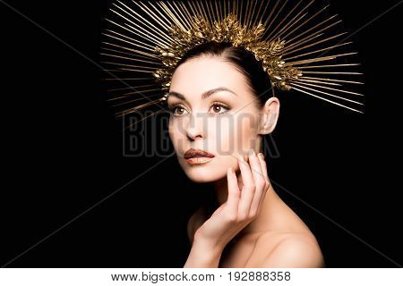 Naked Woman In Golden Headpiece Touching Her Face Isolated On Black