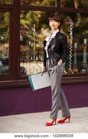 Happy young business woman with a folders walking in city street. Stylish fashion model in leather jacket
