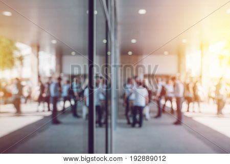 Abstract blur business and entrepreneurship background unrecognizable crowd of businesspeople in front of corporate premises