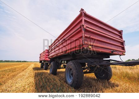 Agricultural tractor trailer in harvested wheat field