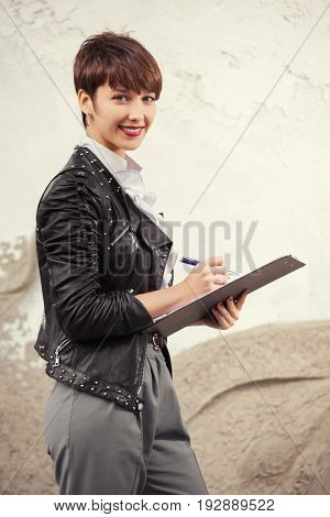 Happy young business woman with clipboard. Stylish fashion female model in black leather jacket