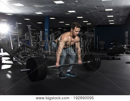 Attractive muscular shirtless athlete doing heavy  deadlift exercise in modern gym. Functional training.