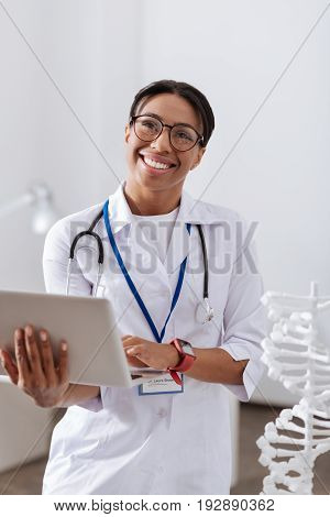 Interesting science. Professional beautiful female scientist holding a laptop and smiling while being interested in her research on genetics