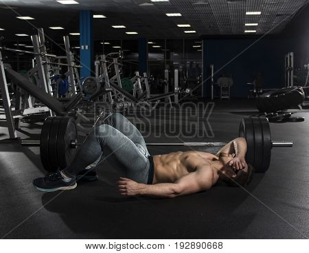 attractive muscular shirtless athlete taking the break from heavy training in modern fitness center. Functional training. Cross workout