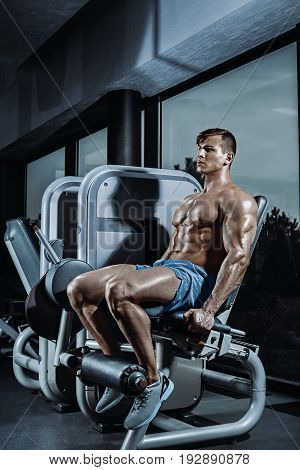 Leg Exercises - Man Doing Leg With Machine In Gym. Sexy muscular man posing in gym