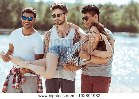three multiethnic men holding attractive asian girl on hands