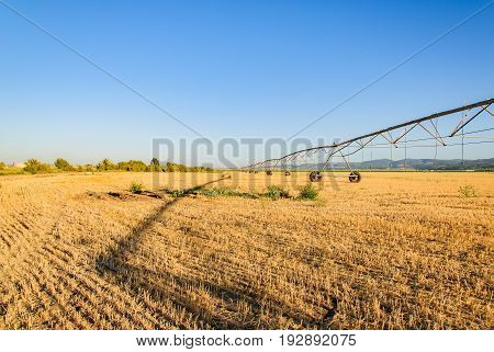 Vanishing point of watering machine  and  his shadow on yellow field.