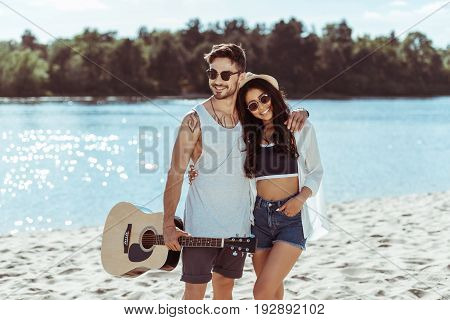 Happy Interracial Couple Embracing On Sandy Beach While Man Holding Guitar