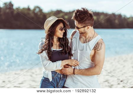Smiling Interracial Couple Embracing And Spending Time Together On Sandy Beach